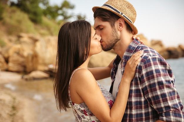 Крупным планом портрет красивой молодой пары в любви, стоя и целуя на пляже