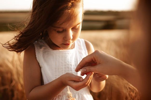 麦畑で白いドレスを着た美しい少女の肖像画を閉じます。すべてのコンセプトの始まり。