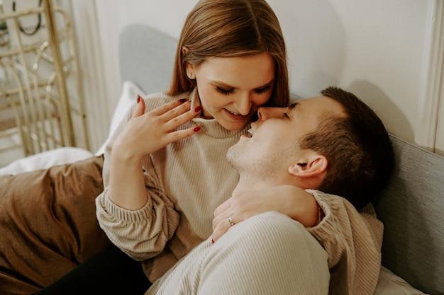 自宅のベッドで美しい若いキスカップルのクローズアップの肖像画。やわらかな色