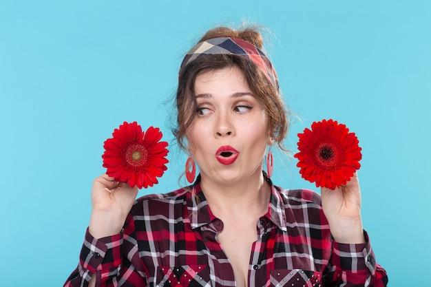 青い壁にポーズをとって手に異なる心を持つ赤い花を保持している美しい若い驚いた女性のクローズアップの肖像画。違いと繊細なニュアンスの概念。