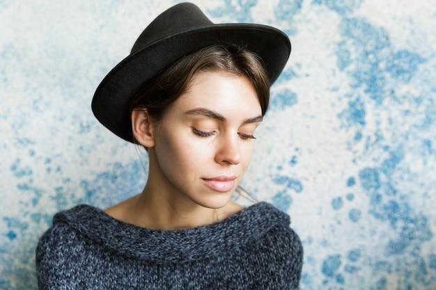 Крупным планом портрет красивой молодой женщины, одетой в свитер и шляпу над синей стеной, с закрытыми глазами