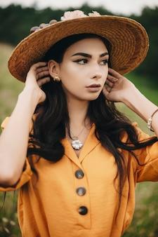 멀리 야외 그녀의 머리를 만지고 찾고 아름 다운 젊은 여자의 초상화를 닫습니다. 모자를 쓰고 검은 머리를 가진 사랑스러운 여성.