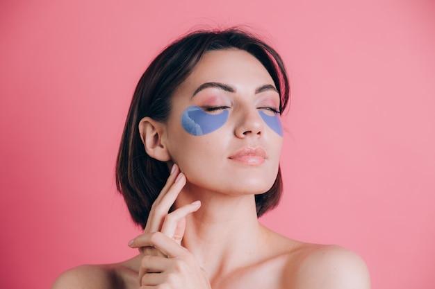 그녀의 눈 아래 파란색 콜라겐 패드와 아름 다운 젊은 여자 토플리스 오픈 어깨의 클로즈업 초상화. 뷰티 개념.