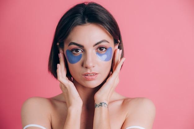 Макро портрет красивой молодой женщины топлес с открытыми плечами с синими подушечками коллагена под ее глазами. концепция красоты.