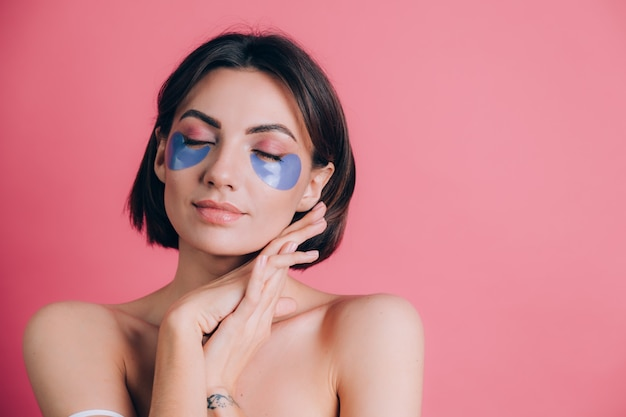 그녀의 눈 아래 파란색 콜라겐 패드와 아름 다운 젊은 여자 토플리스 오픈 어깨의 클로즈업 초상화. 뷰티 개념. 무료 사진