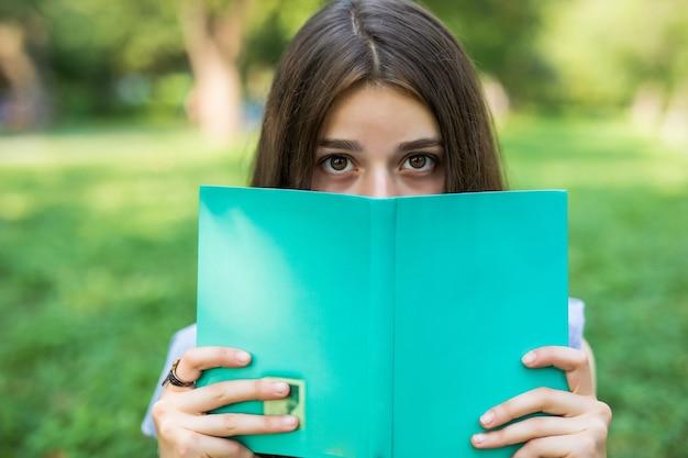 Крупным планом портрет красивой молодой женщины с книгой в парке