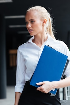 屋外に立っているフォルダーを持つ金髪の女性実業家の肖像画をクローズアップ