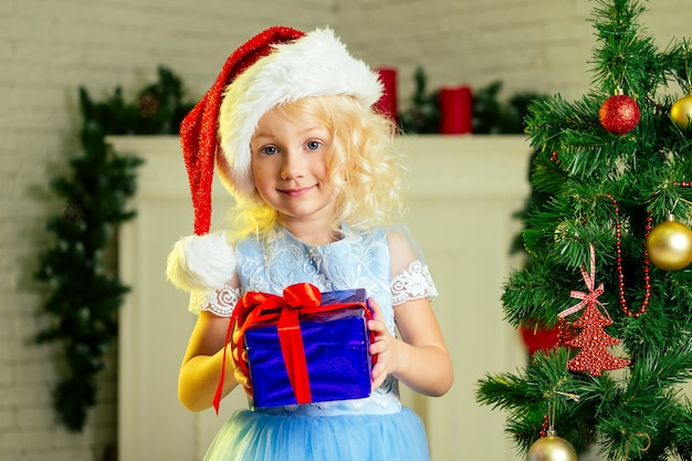 Крупным планом портрет светловолосой кудрявой маленькой девочки в шляпе санта-клауса, с подарком, мечтающей о рождественских чудесах, стоящей рядом с елкой