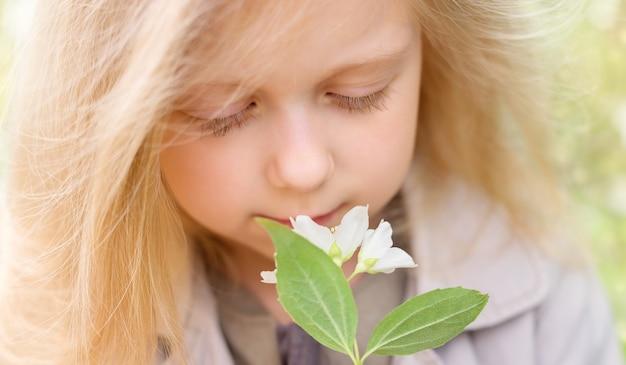 Крупным планом портрет блондинка маленькая девочка нюхает цветы жасмина. мягкий фокус.