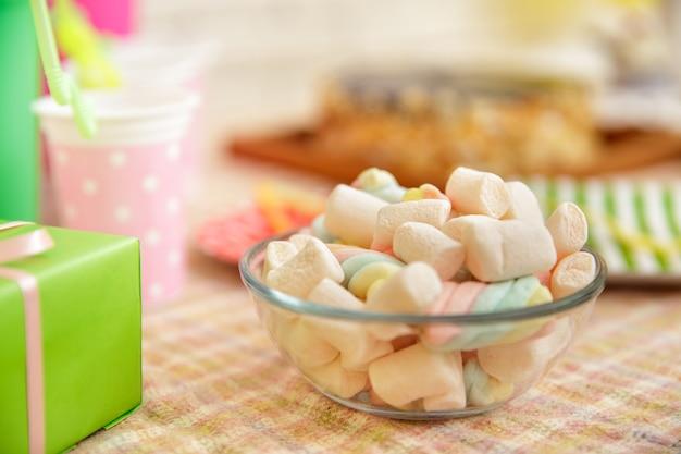 아이의 생일을 위해 설정된 테이블에 마시멜로 가득한 그릇의 초상화를 닫습니다