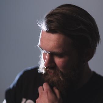 閉じる。陰気なひげを生やした男の肖像画。暗い背景で分離
