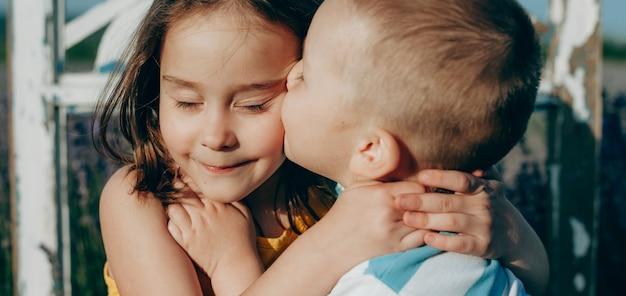 白人の金髪の少年と彼の妹が彼女にキスし、夕日を抱きしめるの肖像画をクローズアップ
