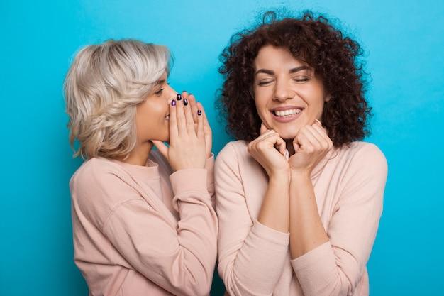 파란색 벽에 포즈를 취하는 동안 그녀의 곱슬 머리 친구에게 뭔가를 속삭이는 백인 금발 소녀의 초상화를 닫습니다