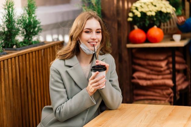 의료 마스크를 착용하고 카페의 배경에 대해 거리에 서있는 백인 여성의 초상화를 닫습니다