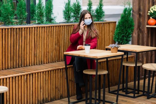 Крупным планом портрет кавказской женщины в медицинской маске, стоящей на улице на фоне кафе