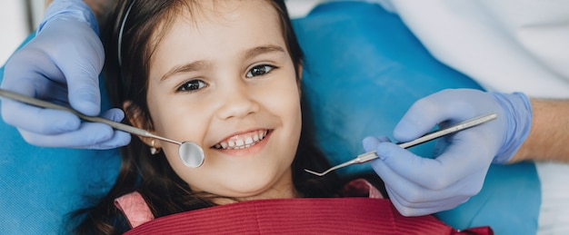 Крупным планом портрет кавказской девушки, проходящей обследование у детского стоматолога, улыбаясь спереди