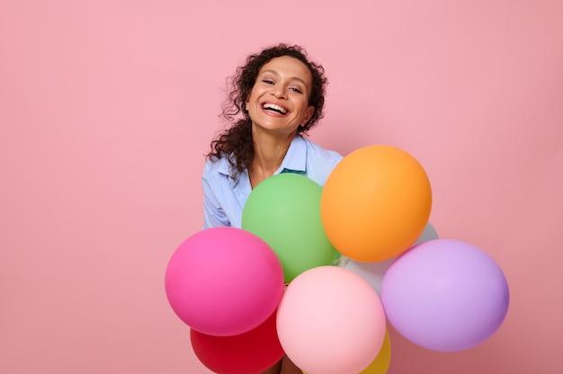 カラフルなマルチカラーの気球、カメラを見て笑い、コピースペースとピンクの背景に分離された魅力的な楽しい混血ヒスパニック系女性のクローズアップの肖像画。