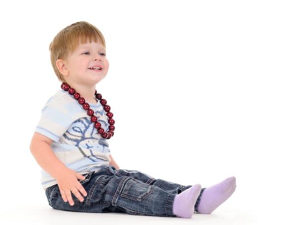 白い壁に魅力的な小さな男の子のクローズアップの肖像画。離乳食と子供のための健康食品の概念。コピースペース