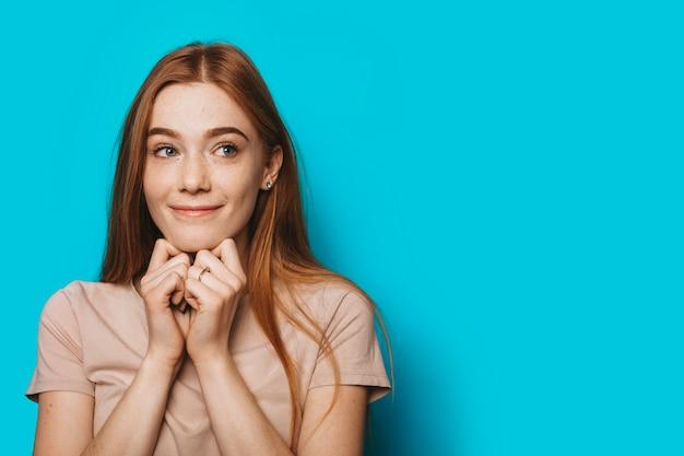 青いスタジオの背景に手で触れて顔を笑顔しながら考えて目をそらしている魅力的な若い女性の肖像画を閉じます。
