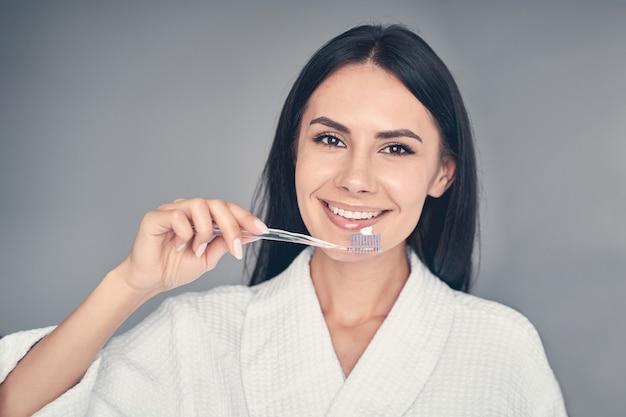 Крупным планом портрет жизнерадостной девушки с красивой улыбкой, держащей в руке зубную щетку