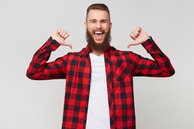 拳を握りしめ、白い背景の上に隔離された喜びで目を閉じて勝者のように自分自身に親指を向けてチェックシャツを着た陽気な幸せなひげを生やした男の肖像画をクローズアップ