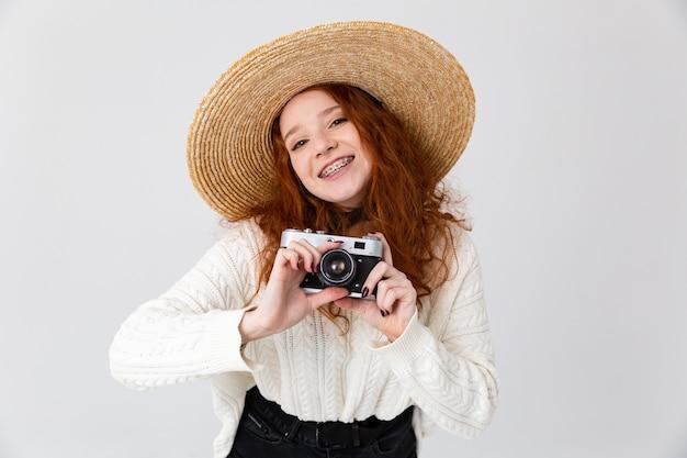 Крупным планом портрет веселой молодой девочки-подростка в летней шляпе, стоящей изолированно на белом фоне, держа фотоаппарат