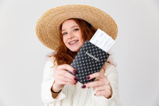 Крупным планом портрет веселой молодой девочки-подростка в летней шляпе, стоящей изолированно на белом фоне, показывая паспорт с авиабилетами