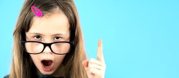 Крупным планом портрет детской школьницы в очках, подняв палец вверх