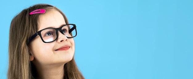 Крупным планом портрет детской школьницы в очках, изолированных на синей поверхности