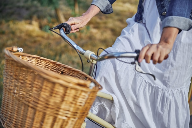 야외에서 나무 바구니와 함께 도시 자전거의 초상화를 닫습니다