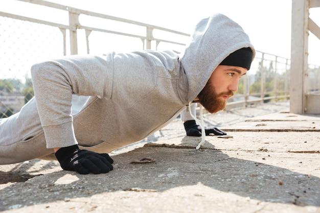 Крупным планом портрет сосредоточенного спортсмена, делающего отжимания на открытом воздухе