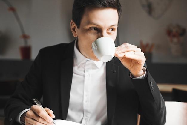 コーヒーを飲みながら彼の毎日の本にメモを書いている自信を持って大人のビジネスマンの肖像画をクローズアップ