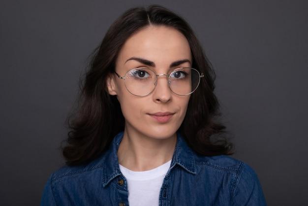 회색 벽 배경에 eyeglasse에서 자신감이 매력적인 젊은 갈색 머리 여자의 초상화를 닫습니다