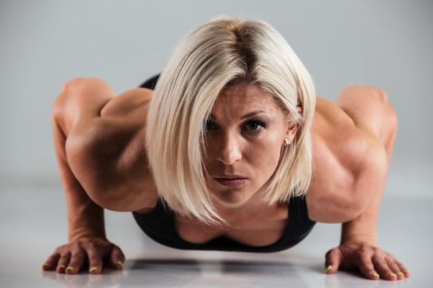 自信を持って筋肉の大人のスポーツウーマンの肖像画を間近します。