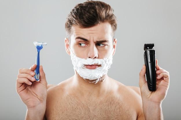 Крупным планом портрет смущенного человека с пеной для бритья