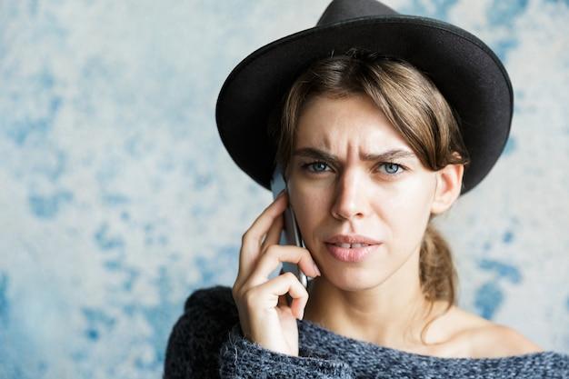 파란색 벽에 휴대 전화에 얘기하는 모자와 스웨터를 입은 혼란 스 러 워 젊은 여자의 초상화를 닫습니다