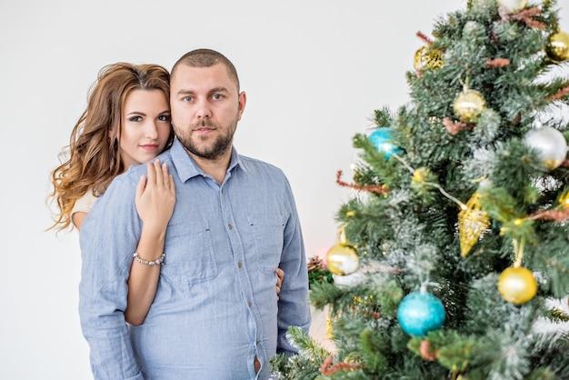 Крупным планом портрет влюбленной пары против елки