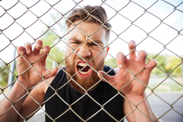 屋外の金属柵で両手で叫んでいる狂ったひげを生やした男の肖像画をクローズアップ