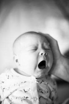 Закройте вверх. портрет плачущего новорожденного. фото в стиле ретро
