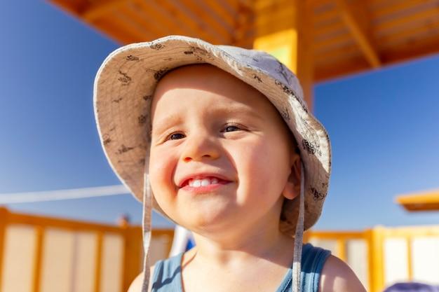 脇を見ているかわいい愛らしい幸せな幼児の男の子の肖像画を閉じます。