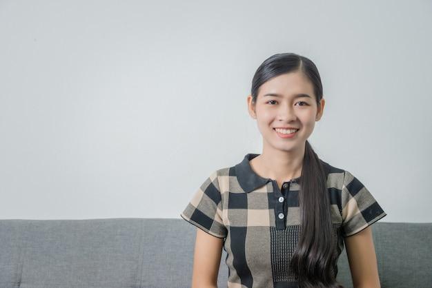 ソファーに座っている間かわいいアジアの女子学生の女の子のクローズアップの肖像画。