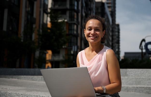 도시의 계단에 앉아 카메라를 보며 웃고 있는 노트북 작업을 하는 혼혈 민족의 귀여운 비즈니스 여성의 클로즈업 초상화. 비즈니스, 원격 원격 작업 및 시작 개념