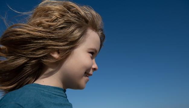 コピースペースで青い空を見ているかわいい小さな子供の肖像画を閉じます。子供の頃と子育ての概念。