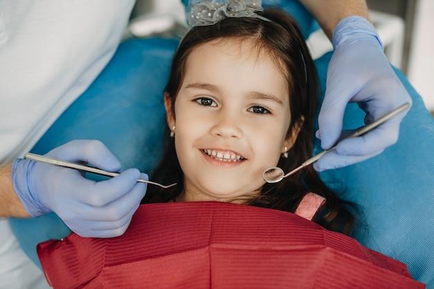치아 검사 전에 웃 고 카메라를보고 귀여운 어린 소녀의 초상화를 닫습니다.