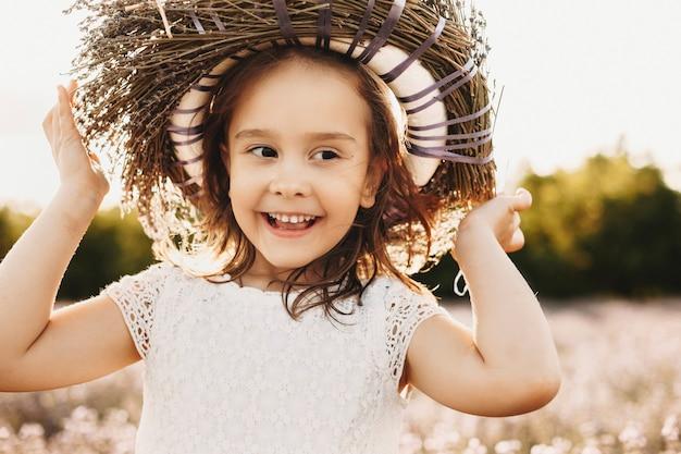 야외 웃는 귀여운 어린 소녀의 초상화를 닫습니다. 멀리 일몰에 웃고 찾고 꽃의 화환을 입고 사랑스러운 아이.