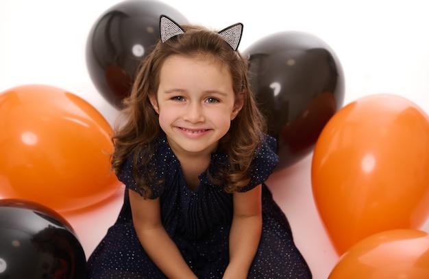 Крупным планом портрет милой маленькой девочки, улыбающейся красивой зубастой улыбкой, смотрящей в камеру на белом фоне с лежащими надутыми воздушными шарами черного и оранжевого цвета. концепция хэллоуина