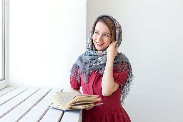 窓の外を見て、何かを考えている彼女の手に本を持っているかわいい若い夢のような女性のクローズアップの肖像画。古典や文学のコンセプト愛好家。