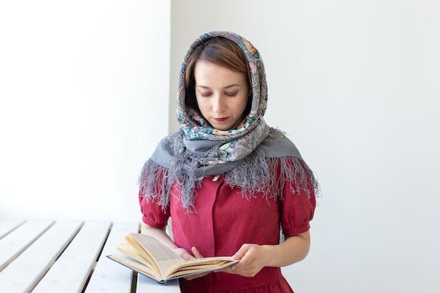 彼女の手に本を持って窓の外を見ているかわいい若い夢のような女性のクローズアップの肖像画と