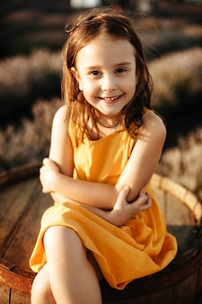 笑顔のカメラを見ている木製の樽に座っているかわいい少女の肖像画を閉じます。