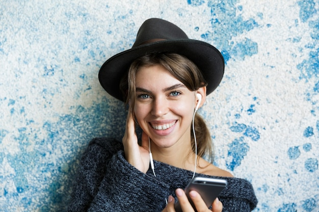 Крупным планом портрет милой молодой женщины, одетой в шляпу и свитер, слушающей музыку с наушниками, держа мобильный телефон над синей стеной